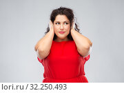 woman in red dress closing her ears by hands. Стоковое фото, фотограф Syda Productions / Фотобанк Лори