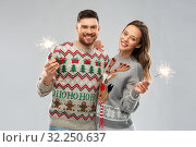 happy couple in christmas sweaters with sparklers. Стоковое фото, фотограф Syda Productions / Фотобанк Лори
