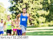 Купить «happy young sportsmen racing wit badge numbers», фото № 32250681, снято 16 августа 2015 г. (c) Syda Productions / Фотобанк Лори