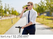 businessman with scooter calling on smartphone. Стоковое фото, фотограф Syda Productions / Фотобанк Лори