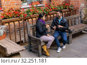 Young man and woman are having fun discussing something while sitting on a bench outdoors. Стоковое фото, фотограф Евгений Харитонов / Фотобанк Лори