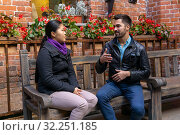 Young man and woman talking gesturing while sitting on a bench outdoors. Стоковое фото, фотограф Евгений Харитонов / Фотобанк Лори