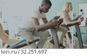 Купить «African man and two Caucasian women exercising on stationary bikes at gym», видеоролик № 32251697, снято 24 марта 2019 г. (c) Яков Филимонов / Фотобанк Лори
