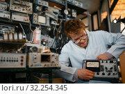 Купить «Crazy scientist holds electrical device in lab», фото № 32254345, снято 17 июня 2019 г. (c) Tryapitsyn Sergiy / Фотобанк Лори