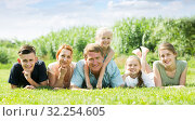 Portrait of modern large family lying together on green lawn outdoors. Стоковое фото, фотограф Яков Филимонов / Фотобанк Лори