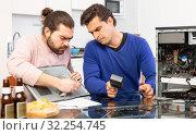 Купить «Men drink beer and repair the desktop computer», фото № 32254745, снято 13 марта 2019 г. (c) Яков Филимонов / Фотобанк Лори