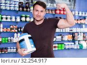 Купить «Athletic man holding sport nutrition supplements, demonstrating muscles», фото № 32254917, снято 12 апреля 2018 г. (c) Яков Филимонов / Фотобанк Лори