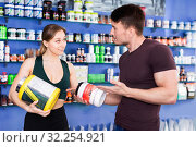 Купить «Smiling sporty guy and girl talking about food supplements in sport nutrition store», фото № 32254921, снято 12 апреля 2018 г. (c) Яков Филимонов / Фотобанк Лори