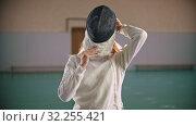 Купить «A young woman fencer put on the helmet», видеоролик № 32255421, снято 10 апреля 2020 г. (c) Константин Шишкин / Фотобанк Лори