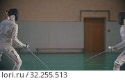 Купить «Two young women fencers in protective suits having a training in the gym in bright lights», видеоролик № 32255513, снято 10 апреля 2020 г. (c) Константин Шишкин / Фотобанк Лори