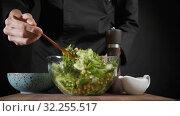 Man mixes vegetarian green salad with the wooden spoon on the dark background. Стоковое видео, видеограф Dzmitry Astapkovich / Фотобанк Лори