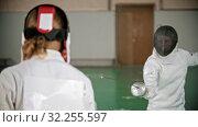 Купить «Two young women in protective costumes at fencing training in the school gym - standing in the position and start fighting», видеоролик № 32255597, снято 1 апреля 2020 г. (c) Константин Шишкин / Фотобанк Лори