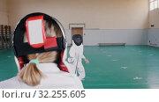 Купить «Two young women in white protective suits having a fencing training - one woman attack and another defends», видеоролик № 32255605, снято 1 апреля 2020 г. (c) Константин Шишкин / Фотобанк Лори