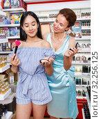 Купить «Girl and mother testing face powder at cosmetics shop», фото № 32256125, снято 21 июня 2018 г. (c) Яков Филимонов / Фотобанк Лори