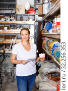 Купить «Young female holding shop list and choosing tools at shelves in build store», фото № 32256353, снято 20 сентября 2018 г. (c) Яков Филимонов / Фотобанк Лори