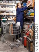 Female worker with basket choosing construction materials at shelves. Стоковое фото, фотограф Яков Филимонов / Фотобанк Лори