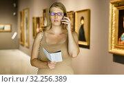 Woman visiting gallery and talking on phone. Стоковое фото, фотограф Яков Филимонов / Фотобанк Лори