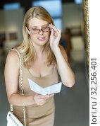 Купить «Woman trying to see picture through glasses», фото № 32256401, снято 22 сентября 2018 г. (c) Яков Филимонов / Фотобанк Лори