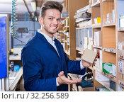 Купить «Male worker choosing items for work», фото № 32256589, снято 7 ноября 2016 г. (c) Яков Филимонов / Фотобанк Лори