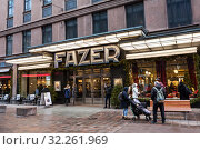 Entrance of the Fazer candy shop decorated with Christmas trees and lights is in center of city. It is one of the largest corporations in the Finnish food industry. Helsinki, Finland (2018 год). Редакционное фото, фотограф Кекяляйнен Андрей / Фотобанк Лори