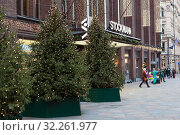 Second entrance of the Stockmann shopping store with Christmas trees in light. Cityscape is at December. The Stockmann is the largest fashion mall in Scandinavia. Helsinki city, Finland (2018 год). Редакционное фото, фотограф Кекяляйнен Андрей / Фотобанк Лори