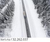 Semitrailer track driving through the blizzard on wintry highway, top view from drone. Стоковое фото, фотограф Кекяляйнен Андрей / Фотобанк Лори