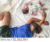 Купить «Two sisters a newborn baby and teenage girl sleeping on bed together, top view», фото № 32262061, снято 23 июня 2019 г. (c) Кекяляйнен Андрей / Фотобанк Лори