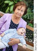 Senior grandmother sitting on becnh with grandchild laying on arms, elder woman with infant portrait. Стоковое фото, фотограф Кекяляйнен Андрей / Фотобанк Лори