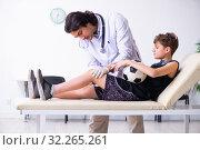 Купить «Boy football player visiting young doctor traumatologist», фото № 32265261, снято 7 мая 2019 г. (c) Elnur / Фотобанк Лори