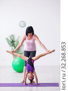 Купить «Girl and mother exercising at home», фото № 32268853, снято 16 июля 2019 г. (c) Elnur / Фотобанк Лори