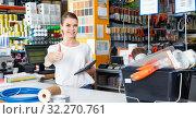 Купить «Young female seller standing at the counter in household tools store», фото № 32270761, снято 17 мая 2018 г. (c) Яков Филимонов / Фотобанк Лори