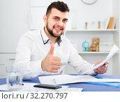 Купить «Smiling young man signing profitable financial agreement», фото № 32270797, снято 5 марта 2017 г. (c) Яков Филимонов / Фотобанк Лори