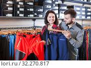 Купить «Couple choosing touristic trousers», фото № 32270817, снято 8 марта 2017 г. (c) Яков Филимонов / Фотобанк Лори