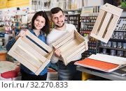 Young couple demonstrating boxes for decorating house in paint store. Стоковое фото, фотограф Яков Филимонов / Фотобанк Лори