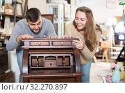Купить «Girl with boyfriend choosing vintage cabinet», фото № 32270897, снято 9 ноября 2017 г. (c) Яков Филимонов / Фотобанк Лори