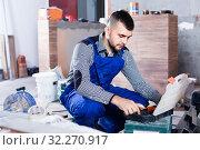 Купить «Builder is choosing tools in suitcase for work», фото № 32270917, снято 3 июня 2017 г. (c) Яков Филимонов / Фотобанк Лори