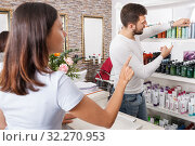 Купить «Young man hairstylist advise woman client in cosmetics studio», фото № 32270953, снято 25 апреля 2018 г. (c) Яков Филимонов / Фотобанк Лори
