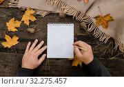 Купить «Human hands with a cup of coffee and scarf at wooden table with notebook and pen and autumn leaves. Human hands with a cup of coffee and scarf at wooden table», фото № 32275457, снято 30 сентября 2019 г. (c) Tetiana Chugunova / Фотобанк Лори