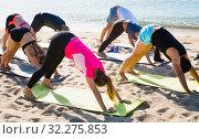 Купить «Sporty people practicing yoga on beach», фото № 32275853, снято 14 июня 2017 г. (c) Яков Филимонов / Фотобанк Лори