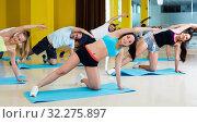 Купить «Group of people practicing yoga in dance hall», фото № 32275897, снято 21 июня 2017 г. (c) Яков Филимонов / Фотобанк Лори