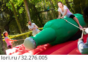 Fun attraction - woman trying to stay on an inflatable bottle. Стоковое фото, фотограф Яков Филимонов / Фотобанк Лори