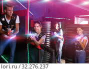Men and girl with colored laser guns playing laser tag game in. Стоковое фото, фотограф Яков Филимонов / Фотобанк Лори