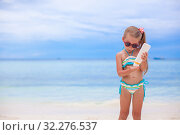 Купить «Little adorable girl in swimsuit holds suntan lotion bottle», фото № 32276537, снято 9 мая 2013 г. (c) Дмитрий Травников / Фотобанк Лори