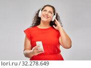 Купить «woman in headphones listens to music on smartphone», фото № 32278649, снято 15 сентября 2019 г. (c) Syda Productions / Фотобанк Лори