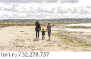 Купить «happy family walking along autumn beach», фото № 32278737, снято 29 сентября 2018 г. (c) Syda Productions / Фотобанк Лори
