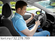 Купить «man or car driver fastening seat belt», фото № 32278789, снято 25 августа 2019 г. (c) Syda Productions / Фотобанк Лори