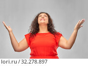 Купить «happy smiling woman in red dress looking up», фото № 32278897, снято 15 сентября 2019 г. (c) Syda Productions / Фотобанк Лори