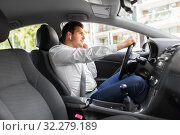 man or driver with wireless earphones driving car. Стоковое фото, фотограф Syda Productions / Фотобанк Лори