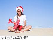 Купить «Счастливая девочка в шапке деда мороза сидит на песке на морском берегу с красным игрушечным самолетиком в руках», фото № 32279481, снято 30 июня 2019 г. (c) Лариса Капусткина / Фотобанк Лори