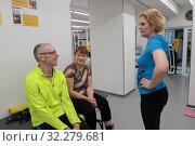 Купить «Инструктор рассказывает, как правильно выполнять упражнение», эксклюзивное фото № 32279681, снято 7 февраля 2018 г. (c) ДеН / Фотобанк Лори